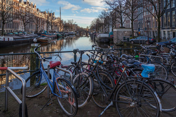 water canals in Amsterdam with a bridge in the middle and traditional architecture with bicycles
