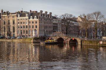 water canals in Amsterdam with a bridge in the middle and traditional architecture