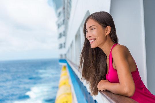 Beautiful Asian model woman on luxury travel cruise vacation in pink dress enjoying the evening on Caribbean getaway holidays. Happy traveler on honeymoon vacations.
