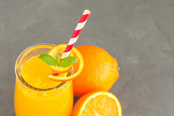 Close-up of a glass of orange juice with oranges fruits
