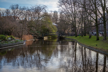 water canals in Amsterdam with a bridge surrounded by trees on a sunny autumn winter day