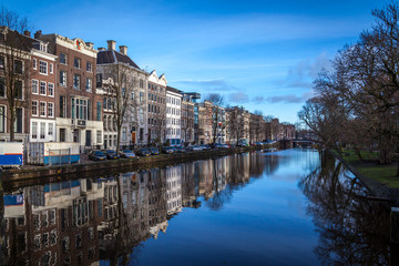 water canals in Amsterdam with traditional architecture reflecting in water on a  sunny day with blue sky