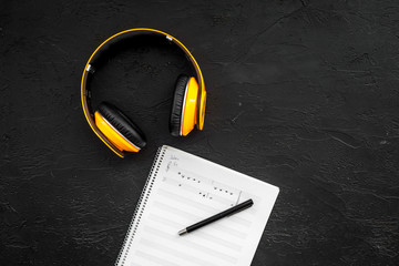 Work desk of modern composer. Music notes near headphones on black background top view copy space