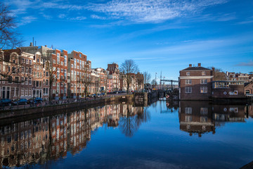 water canals in Amsterdam with blue waters and blue sky on a sunny day with a reflection of traditional buildings in canal's waters