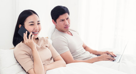 worried woman lying next to her, trying to peek at screen. Cheating and infidelity concept