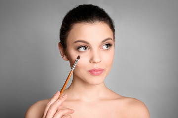 Young woman applying makeup on grey background. Professional cosmetic products