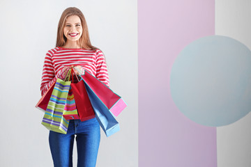 Beautiful young woman with shopping bags on color background