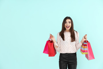 Emotional young woman with shopping bags on color background