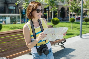 Happy woman tourist travel holding camera and map.