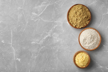 Bowls with different types of flour on light background