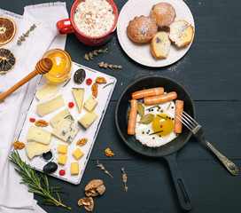 fried eggs with sausages in a black round frying pan and cheese board