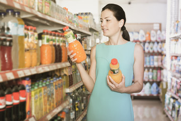 Woman choosing color drinks in bottle