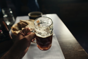 Glass of fresh dark beer in male hand close up