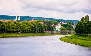 Beautiful cityscape of Uzhgorod town in summer. Embankments with linden and chestnut alley lead to ancient part of a town. Puppet theater and domes of Greek Catholic Cathedral seen in the distance