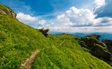 path to the edge of a hill. beautiful mountainous landscape with grassy hillside and giant boulders under. fine weather with blue sky and some clouds