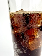 Clear glass of cola over ice against a white background