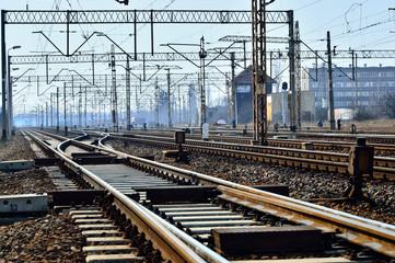 In de dag Spoorlijn Tory kolejowe, słupy i przewody zasilające na tle nieba.