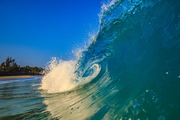 Surfing wave in blue ocean water background