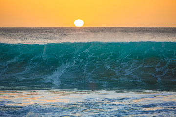 Wall Mural - Sunset background, big surfing ocean wave front view, tropical sea water