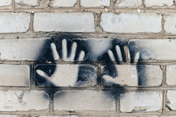 Imprint of two hands on a brick wall.