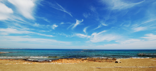 View of the sandy beach of the sea. Clouds