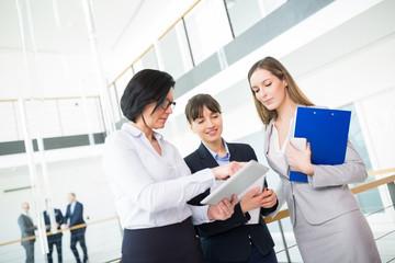 Drei Geschäftsfrauen schauen auf einen Tablet
