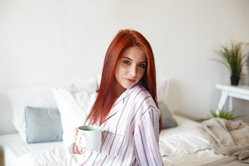 Indoor portrait of gorgeous beautiful young red haired Caucasian female in striped night wear starting new day, enjoying morning coffee, sitting in bedroom with big mug and looking at camera
