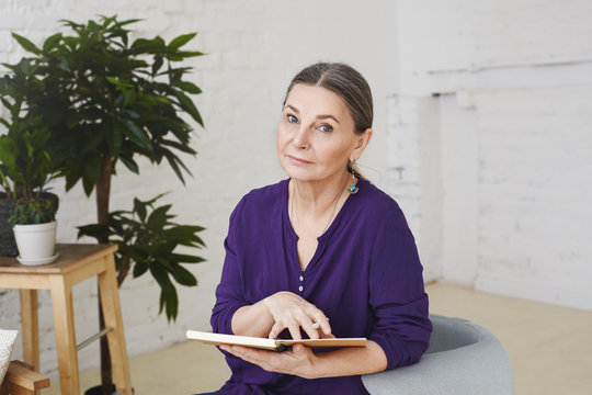 Picture of woman professional psychologist in her fifties waiting for next client, sitting in her modern office on armchair, holding open copybook and looking at camera with serious expression