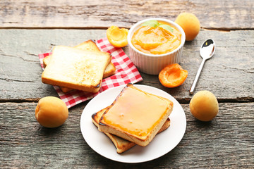 Apricot jam in bowl with bread toasts on grey wooden table