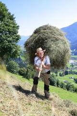 Bergbauer mit Heugabel auf Rücken Schulter Alm