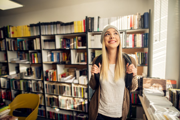 A young please female student is happily looking through the window in front of library bookshelf while holding her backpack sleeves.