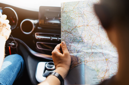 Hipster man holding in male hands and looking on navigation map in auto, tourist traveler hiker driving on background view way road, trip in transportation, person sitting on backdrop window auto
