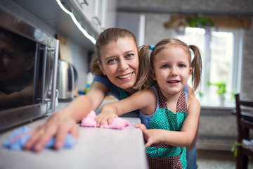 Mother and daughter are cleaning their houses in  kitchen