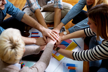Close up view of the young  motivated team of business people putting hands together between them while sitting on the office floor.