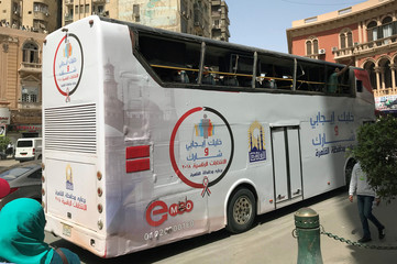 """A bus, with the words reading """"Be positive and come to vote"""", tours the city and calls on citizens to participate in tomorrow's presidential election in Cairo"""