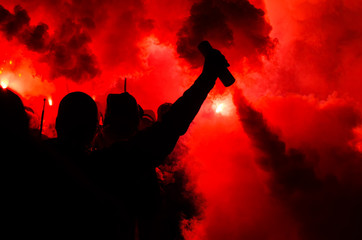 Football fans burn the lights and smoke bombs. The concept of aggression