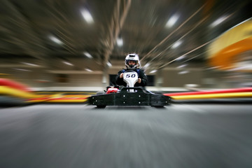 The man is in the go-kart on the karting track