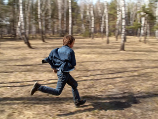 The boy is running in the forest