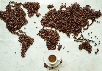 A cup of coffee on the world map which is laid out from coffee beans on a light background