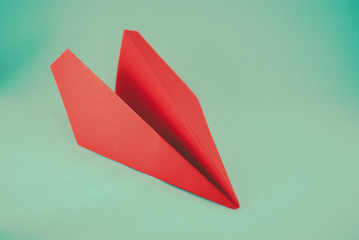 Red paper plane on a white background, isolated. Concept (idea) of airlines, freedom, leadership, success, and creativity