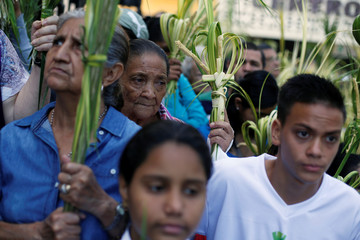 Catholics hold palms in their hands during a mass as they celebrate Palm Sunday, marking the start of the Holy Week, in Tegucigalpa