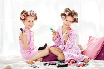 Two beautiful children play cosmetics. Beauty salon. The concept is childhood, fashion, beauty, lifestyle.