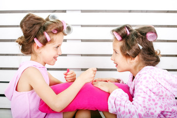 Two fun children are playing with cosmetics. Make a manicure. The concept is childhood, fashion, beauty, lifestyle.