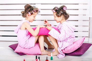 Two fun kids are playing with cosmetics. Make a manicure. The concept is childhood, fashion, beauty, lifestyle.