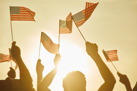 People hold american flags. American rebels at demonstration. Group of people facing the sun and waving small American flags.
