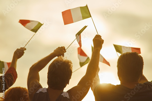 Young people waving italian flags, back view  Italian family against