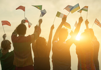 People holding different flags. Back view. Sunny evening sky background.