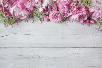 Pink peonies and roses on a wooden background