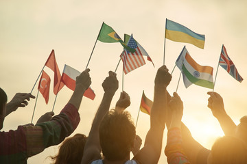 Group of people with various flags. Back view. Sunny evening sky background.