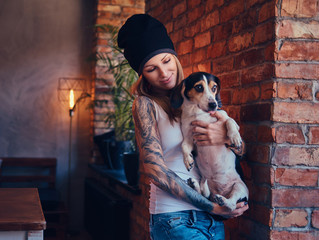 A stylish tattoed blonde female in t-shirt and jeans holds a cute dog.